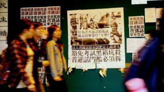 香港浸會大學逸夫校園內一群女學生走過貼上了反對普通話畢業門檻豁免試標語的學生會民主牆(BBC中文網圖片22/1/2018)