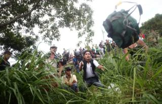A Honduran man catches a backpack thrown to him after crossing the Suchiate river