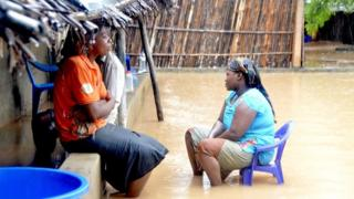 Neighbours chat while sitting in a flooded street of the Paquite district of Pemba
