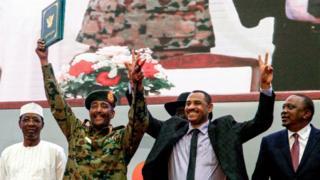 Ahmad Rabie (à droite), l'un des leaders des manifestations pro-démocratie, aux côtés du général Abdel Fattah al-Burhan, le chef du Conseil militaire de transition, lors de la signature du nouvel accord de partage du pouvoir, samedi 17 août, à Khartoum.