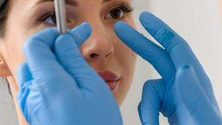 woman having her nose examined