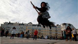Участница Парада зомби в Киеве прыгает на метле накануне праздника Хэллоуин 27 октября 2018 года
