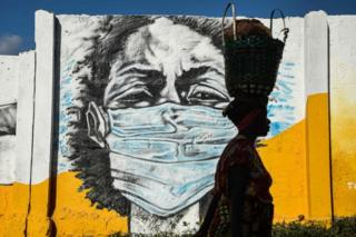 A Tanzanian woman carries a basket on her head as she walks in front of a mural depicting a masked person.