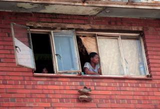 A woman looks out of her window in Harare
