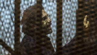 Egyptian activist and blogger Alaa Abdel Fattah inside defendant's cage during his trial in Cairo on 23 May 2015