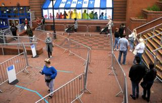 Customers follow barriers to safely social distance outside a shopping centre