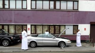 Worshippers bless a vehicle