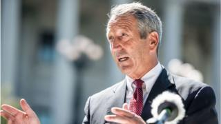 Former South Carolina Gov Mark Sanford speaks to the media with a cardboard cutout of President Donald Trump during a campaign stop at the state house in September
