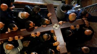 Worshippers carry a large wooden cross into a church in Jerusalem