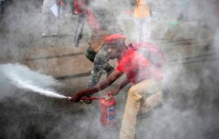 """An EFF supporter sprays a fire extinguisher as members and supporters of the South African opposition party, the Economic Freedom Fighters (EFF), demonstrate against South Africa""""s president Jacob Zuma"""