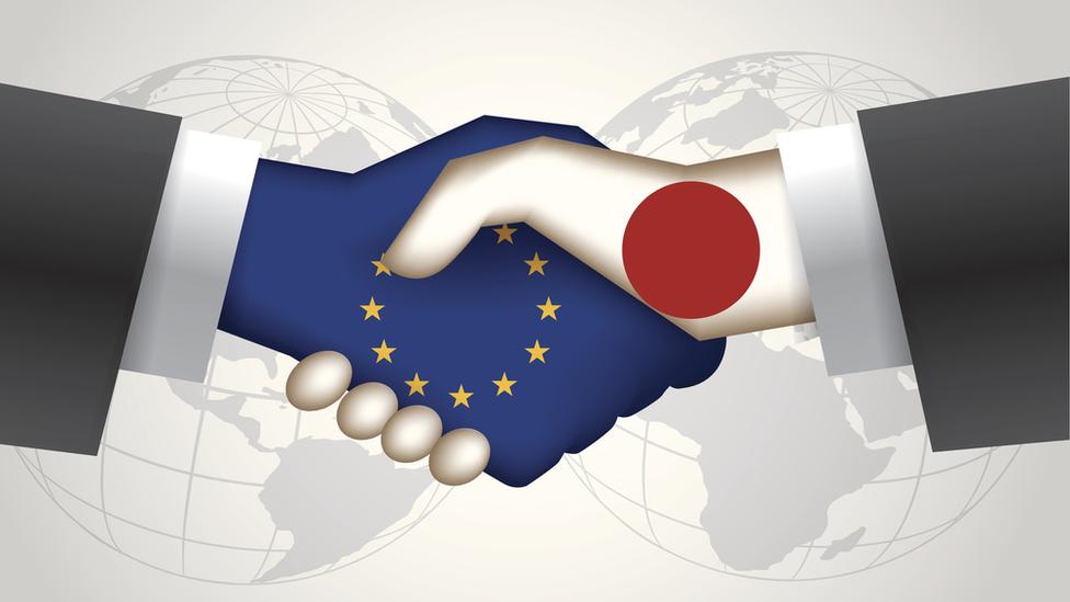 Manos con banderas de la UE y Japón estrechándose en señal de acuerdo.