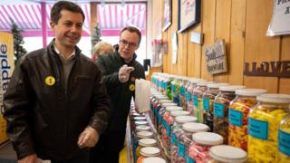 Democratic presidential hopeful Pete Buttigieg and his husband Chaster (R) visits a sweet shop in Littleton, New Hampshire on 10 November 2019