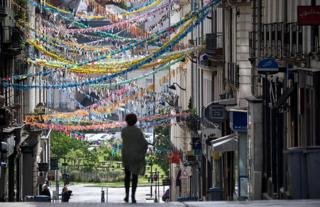 A woman walks down a street decorated with dozens of handmade garlands