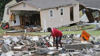 A man sorts through debris following severe flooding