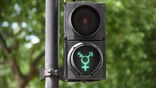 A green transgender symbol on a pedestrian crossing light in Trafalgar Square