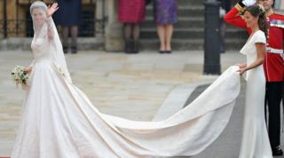 Catherine Middleton waves as she walks towards Westminster Abbey with Pippa Middleton holding her train.