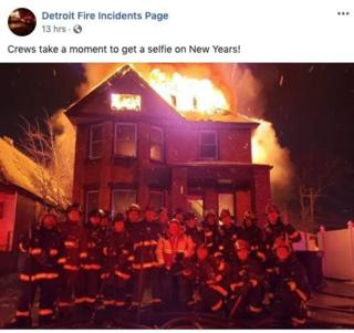 the photo of firefighters posing in front of a burning building