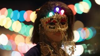 A girl wearing a mask takes part in a procession celebrating the religious holiday of Mawlid al-Nabi, the birthday of Prophet Mohammad, in Benghazi, Libya December 10, 2016. Picture taken December 10, 2016