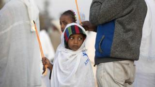A young boy holds a candle during the Timket, an Epiphany festival, in Addis Ababa, on January 19, 2018.