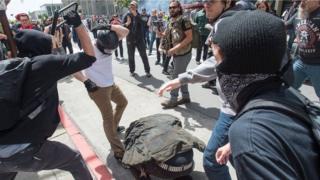 一名男子用自行车锁殴打另一名倒在地上的男子。