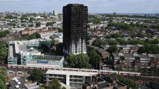 Grenfell Tower with a Tube train passing nearby