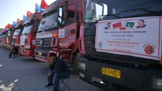 A Chinese worker sits near trucks carrying goods during the opening of a trade project in Gwadar port in 2016.