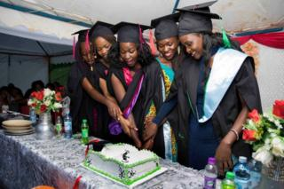 Ruth Akulu (right) and colleagues cut a cake together.
