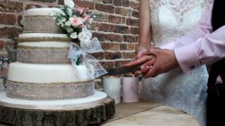 Newly-weds cutting a wedding cake