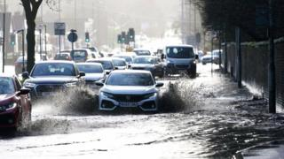 Cars drive through floodwater in Manchester