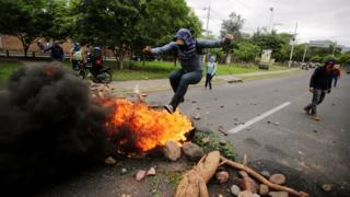 A demonstrator jumps on a barricade during a protest against the government of Honduras' President Juan Orlando Hernandez, in Tegucigalpa