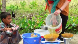 Dr Theresa Dankovich pouring dirty pond water into a filter funnel in rural Bangladesh
