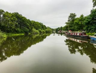 Canal boats reflected in a canal