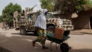 A woman pushes a wheelbarrow carrying a jerrycan filled with water as Nigerian soldiers patrol in the town of Banki in northeastern Nigeria on April 26, 2017