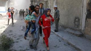 Syrians run for cover following a reported air strike on the rebel-held district of Qatarji, Aleppo (29 April 2016)