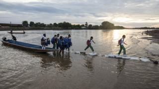 School kids and others disembark from small canoes