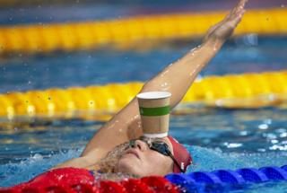 Jenny Mensing of Germany swims backstroke with a paper cup on her forehead while warming up at the Glasgow 2018 European Swimming Championships in Glasgow, UK