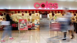 A Coles supermarket is seen, with blurred shoppers wheeling carts outside