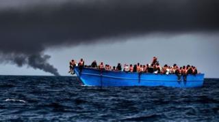 ผู้อพยพจำนวนหนึ่งนั่งแออัดยัดเยียดบนเรือล่องในทะเลเมดิเตอร์เรเนียน