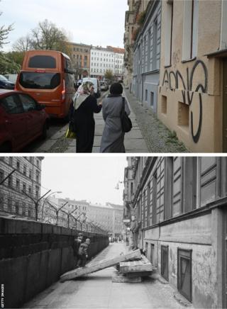 Two women walk along Sebastianstrasse, along which the Berlin Wall once ran, on October 2019. The photo underneath shows the same location in 1963