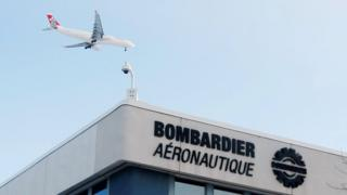 A plane flies over a Bombardier plant in Montreal, Quebec, Canada