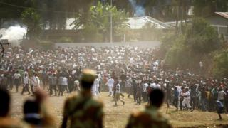 Soldiers watch protestors run from tear gas during a festival in Oromia, October 2, 2016