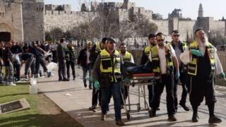 Ultra-Orthodox Jewish Zaka volunteers carry away on a stretcher the body of a Palestinian who was shot dead during a stabbing attack next to the Jaffa Gate of Jerusalem's Old City on 23 December 2015