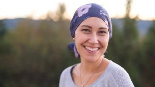 Mujer sonriente con un pañuelo en la cabeza.