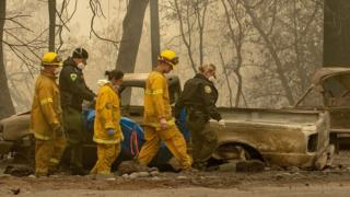 Rescue crews walk through the burnt remains of Paradise in California, November 2018