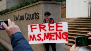 A man holds a sign outside of the B.C. Supreme Court bail hearing of Huawei CFO Meng Wanzhou, who is being held on an extradition warrant in Vancouve