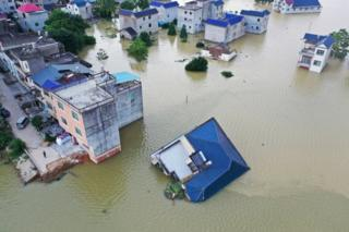 A building that has fallen over after flooding is seen partially submerged in floodwaters following heavy rainfall in the region, at a village near Poyang Lake, in Poyang county, Jiangxi province, China July 13, 2020