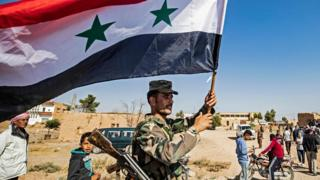 A Syrian regime soldier waves the national flag