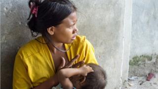 Mujer latinoamericana amamantando a su bebé.
