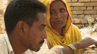 Safia Bibi feeds her mentally ill son rice