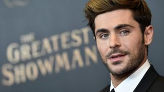 Zac Efron looking wistful, with 'The Greatest Showman' written behind him.